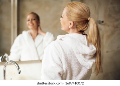 Beautiful woman wearing a bathrobe. Young happy woman enjoing in hotelroom.