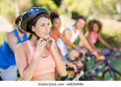 Beautiful woman wearing bicycle helmet in park