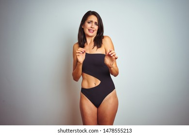 Beautiful woman wearing bikini swimwear over white isolated background disgusted expression, displeased and fearful doing disgust face because aversion reaction. With hands raised. Annoying concept.
