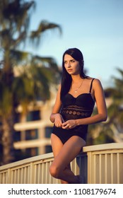 Beautiful woman wearing black bikini by the pool in summer scenery.