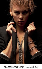 Beautiful woman wearing black jacket with chains on her arms and neck