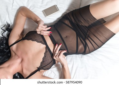 Beautiful woman wearing black lingerie in bedroom