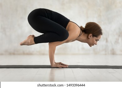 Beautiful woman wearing black sportswear practicing yoga, doing Crane exercise, standing in Bakasana pose on mat, attractive sporty girl working out at home or in yoga studio with grey walls