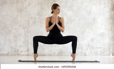 Beautiful woman wearing black sportswear practicing yoga, standing in Goddess pose on mat, attractive girl doing Sumo Squat exercise, working out at home in modern yoga studio with grey walls