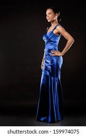 beautiful woman wearing blue evening dress on black background