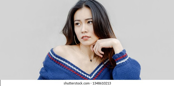 Beautiful woman wearing blue sweater thinking looking to side isolated against grey background.