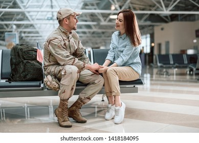Beautiful woman wearing casual and situating opposite her husband in military uniform. They are holding hands while siiting near each other indoors. Homecoming concept