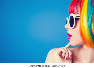beautiful woman wearing colorful wig and white sunglasses against blue background - Shutterstock ID 286104992
