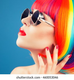 beautiful woman wearing colorful wig and silver sunglasses against blue background