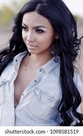 Beautiful woman wearing denim with long dark hair.  Shot in the Arizona Desert,USA.