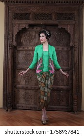 beautiful woman wearing an elegant kebaya, kebaya is a traditional dress worn by Indonesian and Malaysian women made from gauze cloth worn with batik.