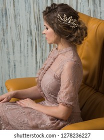 Beautiful woman wearing evening lace dress pink blush color with makeup and hairstyle decorated by pearl hair accessory
