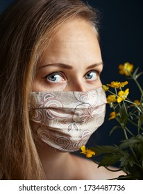 Beautiful woman wearing a face handmade floral mask, looking at camera, close up on dark background. Flu epidemic, dust allergy, protection against virus. City air pollution concept