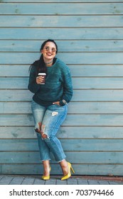 Beautiful woman wearing fall sweater, ripped jeans and colorful shoes drinking take away coffee standing against cafe wall on city street. Casual fashion, elegant everyday look. Plus size model.
