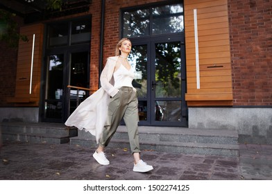 Beautiful Woman Wearing Fashionable Spring, Fall Clothes (beige trench coat, oversize khaki cargo pants, accessorie) Outdoors. Female stylish Model walking city Street. Autumn trend, fashion outfit