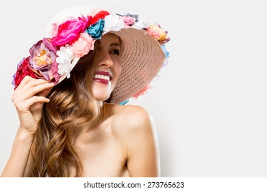 Beautiful woman wearing flower hat over white background