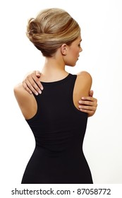 beautiful woman wearing hair in french roll updo in sexy black dress standing with her back against white background