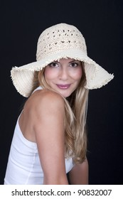 Beautiful woman wearing a hat, on black background