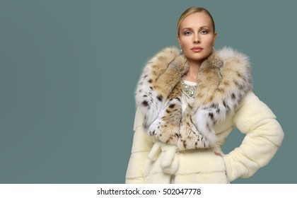 Beautiful woman wearing luxury white lynx fur coat. Winter fashion model.