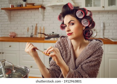 Beautiful woman wearing makeup, funny hair curlers and housecoat sitting at kitchen table at home, filing nails, squinting and smirking. Young wife scheming cunning plan and pondering choices