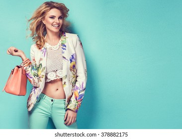 Beautiful woman wearing nice clothes, handbag posing on turquoise background. Fashion spring photo