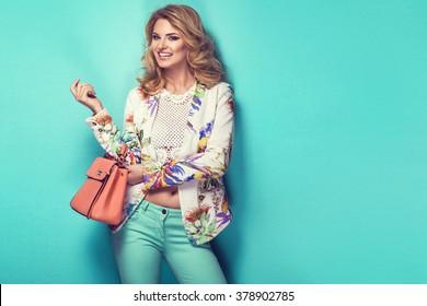 Beautiful woman wearing nice clothes, handbag posing on turquoise background. Fashion spring photo
