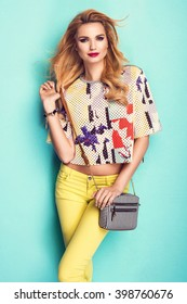 Beautiful woman wearing nice clothes, handbag posing on turquoise background. Fashion spring photo. Bright colors