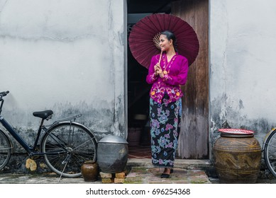 Beautiful woman wearing Nyonya dress her hand holding paper umbrella with old house, The dress of Paranakan woman in southeast asia, Chinese Malay mix Traditional costume, Ranong, Travel in Thailand