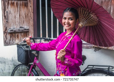 Beautiful woman wearing Nyonya dress her hand holding paper umbrella with bicycle and old wooden window, The dress of Paranakan woman in southeast asia, Chinese Malay mix