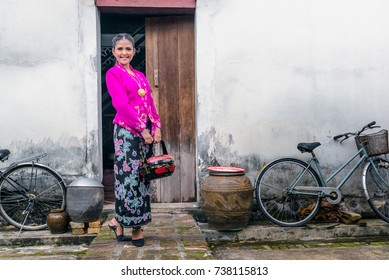 Beautiful woman wearing Nyonya dress her hand holding vintage food carrier with old house, The dress of Paranakan woman in southeast asia, Chinese Malay mix