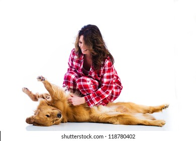 Beautiful woman wearing red flannel pajamas with her handsome golden retriever dog.
