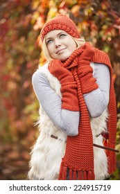beautiful woman wearing red hat gloves and scarf against colorful autumn tree