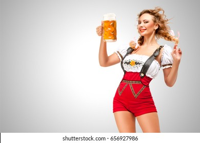 Beautiful woman wearing red jumper shorts with suspenders as traditional dirndl, serving two beer mugs on grey background.