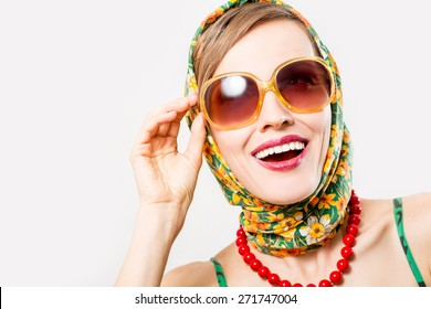 Beautiful woman wearing scarf and sunglasses over white background