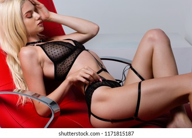 Beautiful woman wearing sexy lingerie and sitting in the red chair