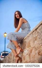 Beautiful woman wearing striped overalls and stylish sandals sitting on a stone wall outdoors. Young girl posing in the old part of the town. Fashion and lifestyle.