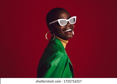 Beautiful woman wearing stylish sunglasses and smiling against red background. African female model wearing funky sunglasses.