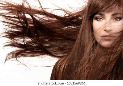 Beautiful woman wearing subtle makeup with gorgeous healthy long brown hair blowing to the side in a breeze in a hair care and beauty concept isolated on white in a close up cropped view