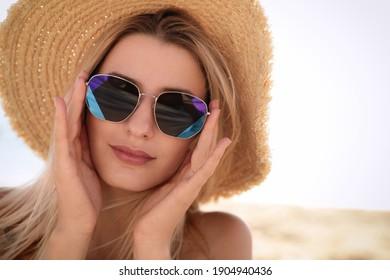 Beautiful woman wearing sunglasses outdoors on sunny day, closeup