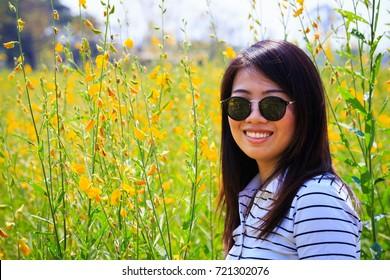 beautiful woman wearing sunglasses in sunn hemp flowers field