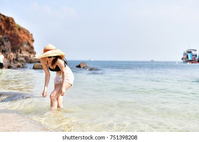 Beautiful woman wearing a swimsuit playing in the beach.