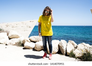 Beautiful woman wearing in t-shirt, blue jeans and sunglasses, She stays near coast line and laugh