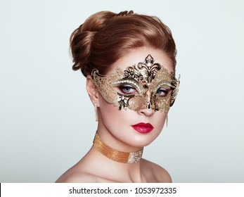 Beautiful Woman Wearing Venetian Masquerade Carnival Mask at Party, over White Background. Christmas and New Year Celebration. Sexy Girl with Holiday Makeup and Red lips. Golden Mask