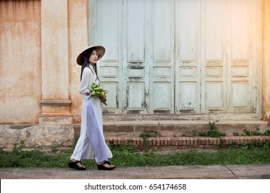 Beautiful woman wearing a Vietnamese dress Ao Dai holding lotus In abandoned buildings.