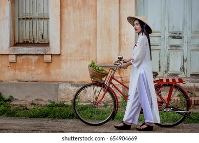 Beautiful woman wearing a Vietnamese dress Ao Dai  with red bike in abandoned building.