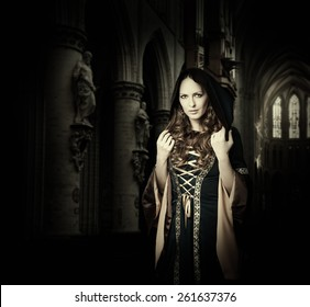 Beautiful woman wearing vintage medieval dress with hood in gothic church