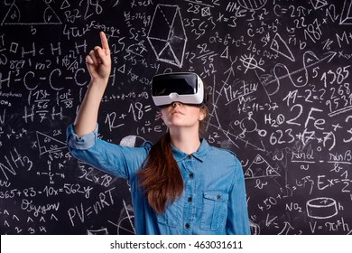 Beautiful woman wearing virtual reality goggles against big blac