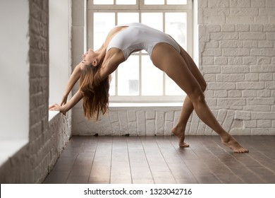 Beautiful woman wearing white body practicing yoga, standing in Wild Thing pose, attractive sporty girl doing Camatkarasana exercise, working out at home or in modern yoga studio with big windows