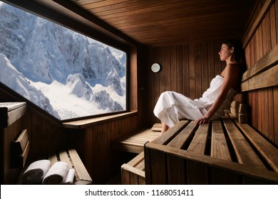 A beautiful woman wearing a white towel takes a sauna: The sauna is made of wood with a large window with a view of the mountain. Concept of: relax, vacation, wellness center.