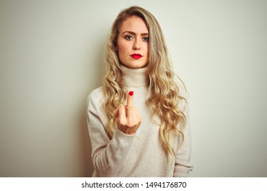 Beautiful woman wearing winter turtleneck sweater over isolated white background Showing middle finger, impolite and rude fuck off expression